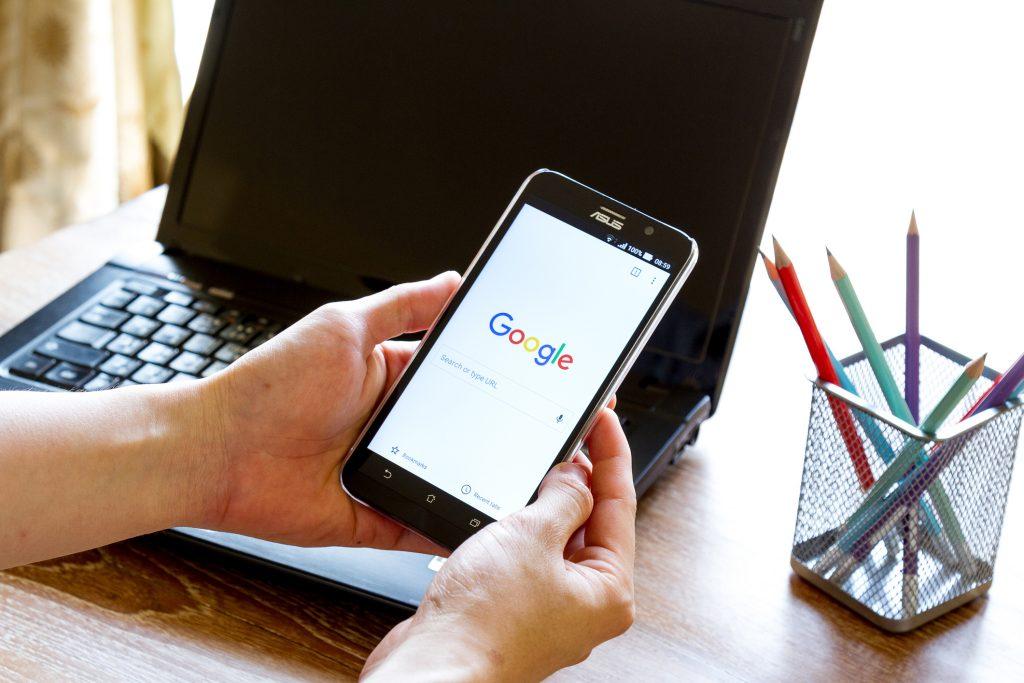 Telefon z wyszukiwarką google na ekranie, w tle laptop oraz ołówki